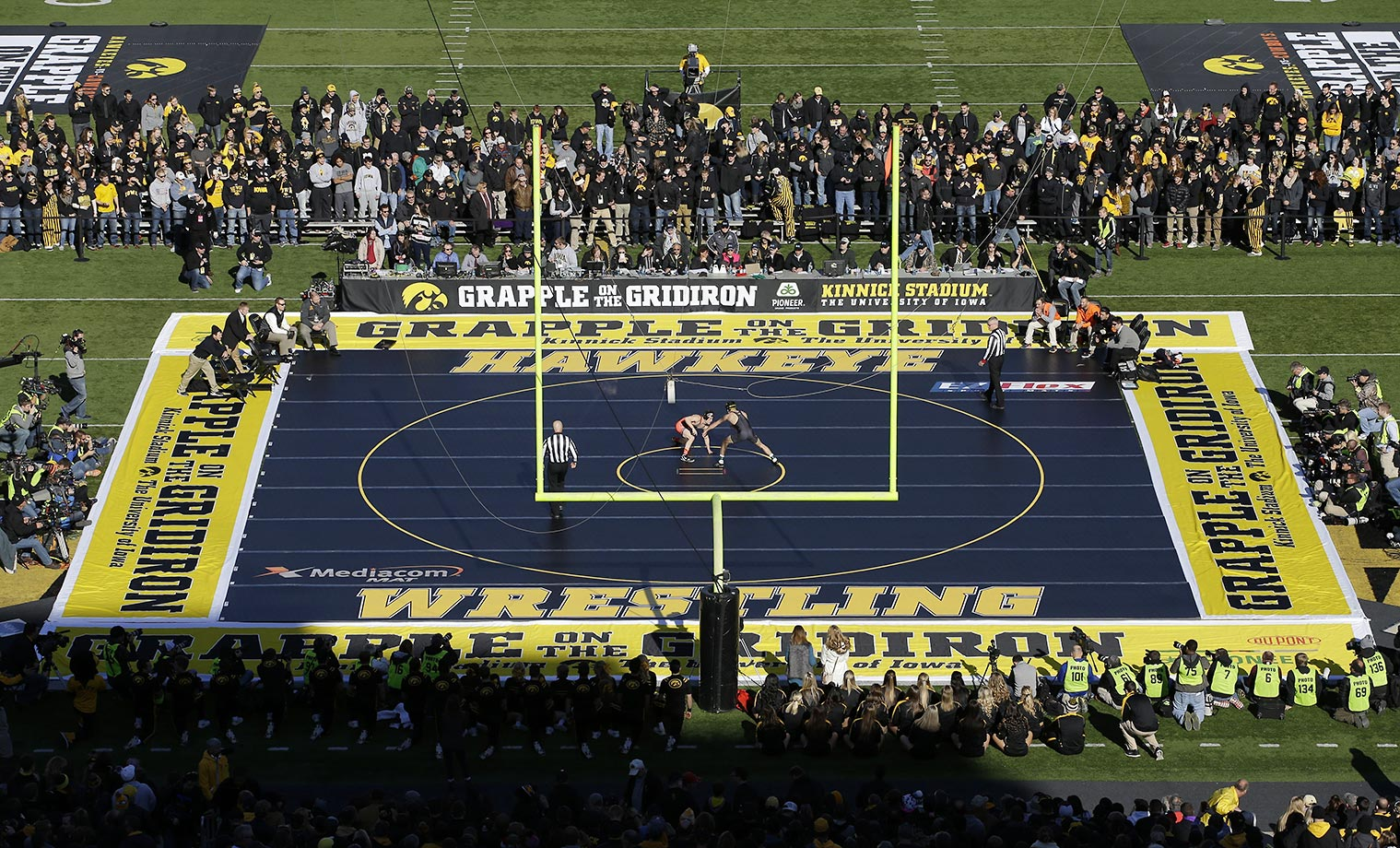 Oklahoma State and Iowa grapple during an NCAA college wrestling match that took place on the football field at Kinnick Stadium.