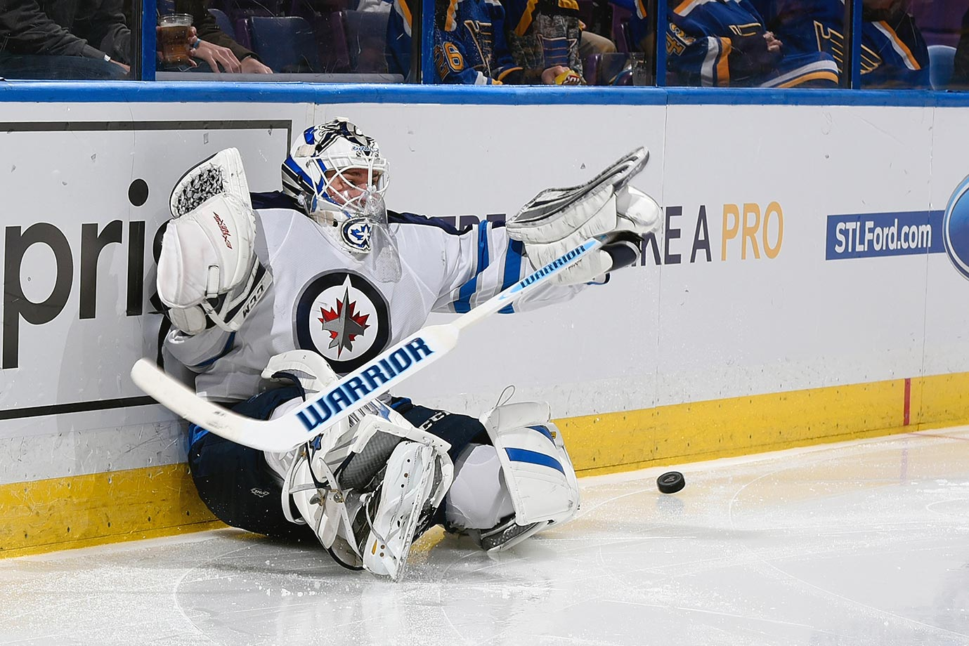 Michael Hutchinson of the Winnipeg Jets falls to the ice chasing a puck in a game against the St. Louis Blues.