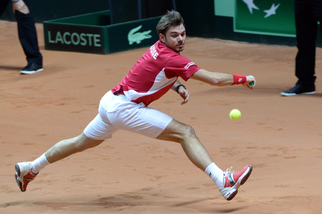 Wawrinka returns a backhand to Tsonga during the first match of the Davis Cup final.