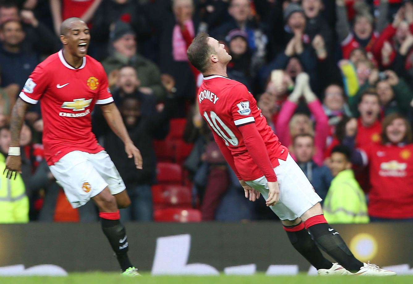 Wayne Rooney of Manchester United celebrates scoring his third goal by pretending to knock himself out.
