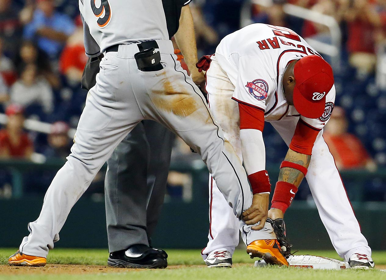 Yunel Escobar of the Nationals playfully attempts to pick up Dee Gordon, who was safe at third on a triple. The Marlins won 2-1.