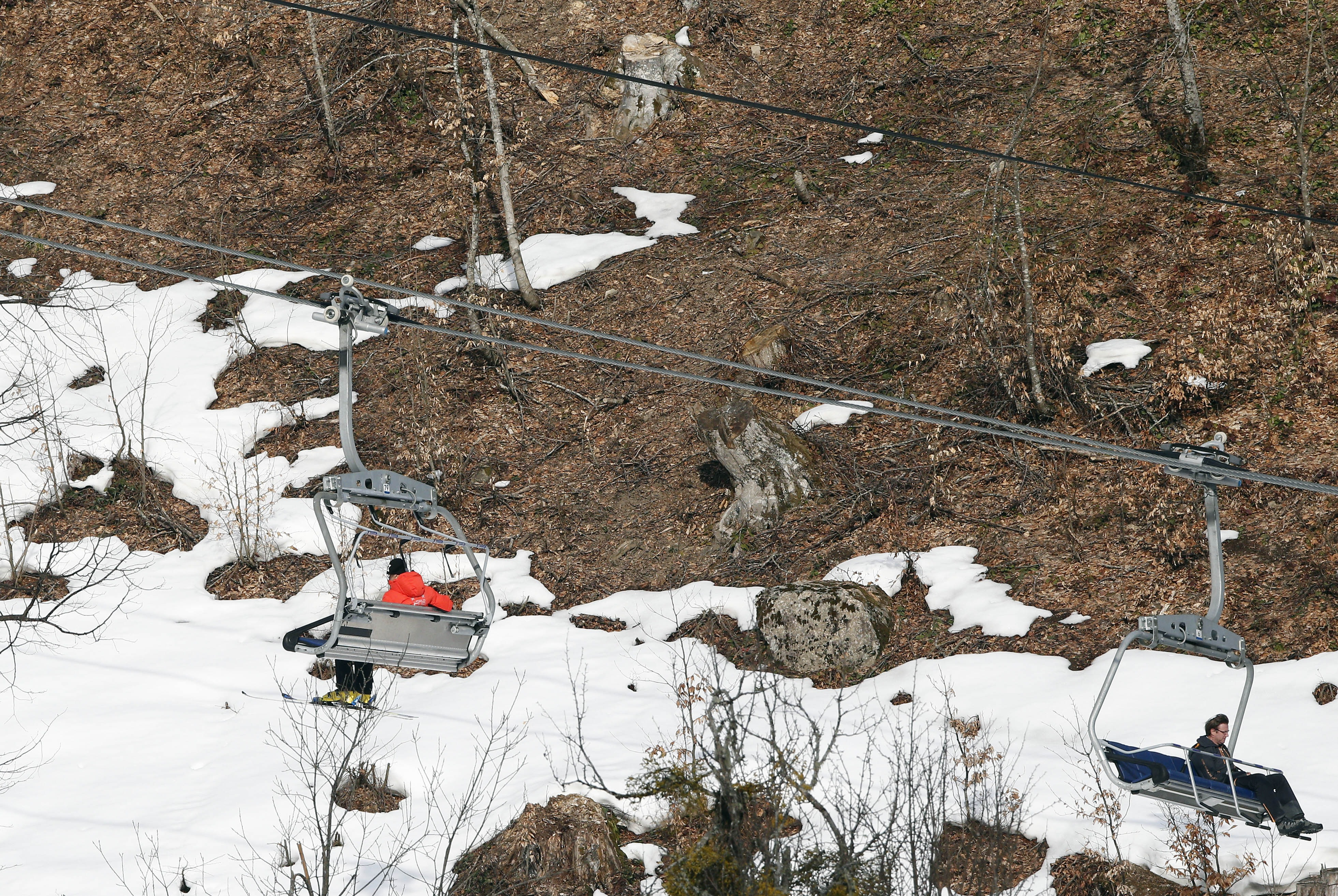 People take a ski lift past patches of snow at the Sochi 2014 Winter Olympics, Tuesday, Feb. 11, 2014, in Krasnaya Polyana, Russia. Warm temperatures in the mountains was a factor in the cancellation of Women's downhill training on Tuesday. (AP Photo/Christophe Ena)