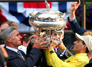 Union Rags trainer Michael Matz and jockey John Velazquez display the trophy in the winners circle after Saturday's Belmont Stakes.