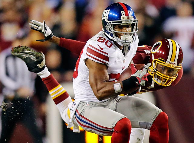 Giants receiver Victor Cruz reels in a pass despite pressure from Redskins defensive back Cedric Griffin.