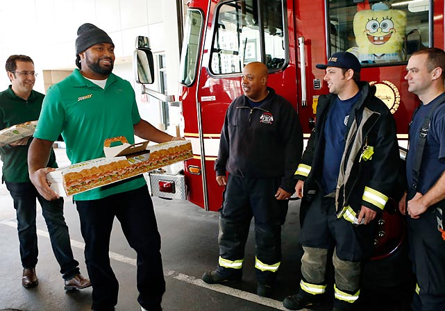"""The SUBWAY Guy"" (left) and Patriots linebacker Mayo (fitting last name for tackling sandwiches) paid a surprise visit to the Boston Fire Department. The chief (in the window of the truck) was clearly delighted."