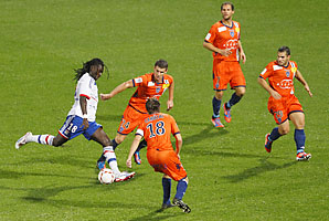 Bastia players surround Lyon's Bafe Gomis in a Ligue 1 match earlier this season.