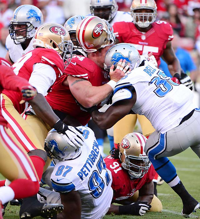 The typically ferocious 49ers defensive tackle Justin Smith loses his helmet trying to tackle running back Joique Bell of the Lions.