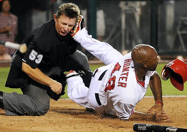 Umpire Greg Gibson gets a spike to the face from the Angels' Torii Hunter.