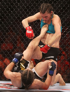 Liz Carmouche kicks her opponent Colleen Schneider in the chest during a 2010 bout.