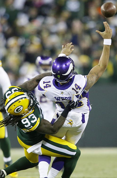 Joe Webb tosses a desperation pass before being taken down by Packers linebacker Erik Walden.