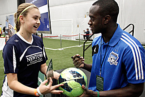 Marcus Tracy, a native of Newtown, visits with 12-year-old Newtown soccer player Greta Staubly.