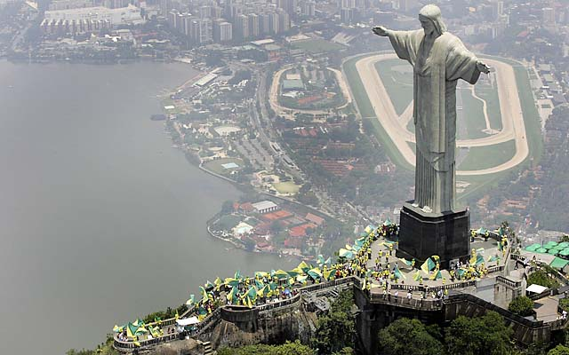 People wave flags at the Christ the Redeemer statue after Brazil was chosen as host of the 2014 World Cup.