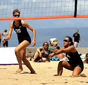 Two players from the University of Hawaii take place in a sand volleyball exhibition.
