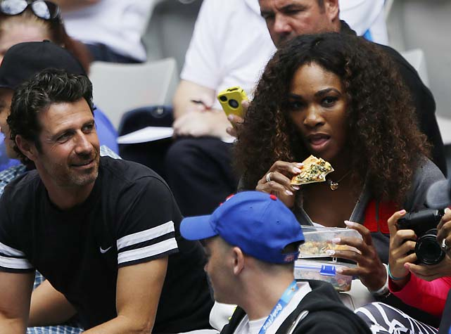 Serena Williams eats pizza while watching sister Venus play.