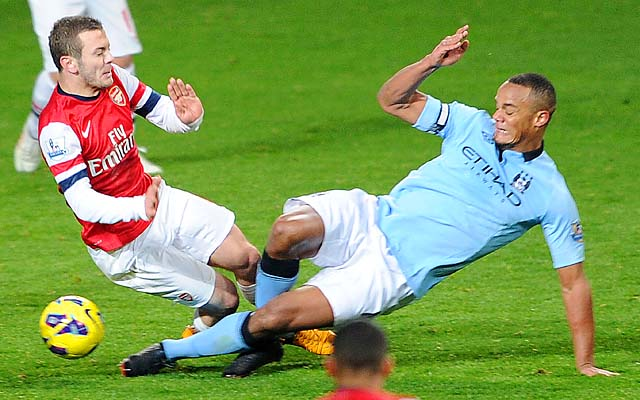 Vincent Kompany (right) was given a straight red card for this challenge on Jack Wilshere.