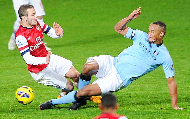Vincent Kompany (right) was given a red card for this challenge on Jack Wilshere