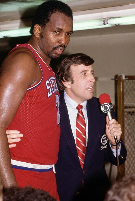 Moses Malone towers over Musburger during a postgame interview after Malone's Philadelphia 76ers finished off the Los Angeles Lakers in Game 4 of the 1983 NBA Finals.