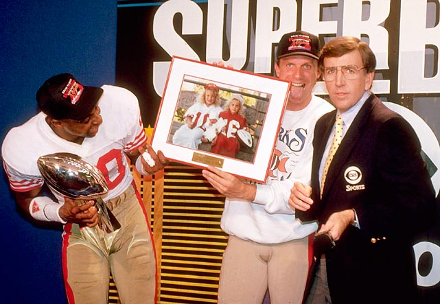 Jerry Rice holds the Vince Lombardi Trophy and Joe Montana holds a framed photo of his daughters while the San Francisco 49ers duo talk with Musburger after beating the Broncos to win Super Bowl XXIV.