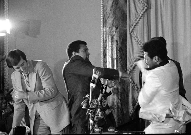 Musburger dodges the fake blows of boxers Muhammad Ali and Leon Spinks, who pretend to fight during a press conference.