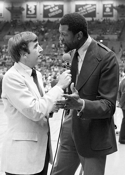 Brent Musburger talks with basketball legend Bill Russell before an NBA game in 1980.