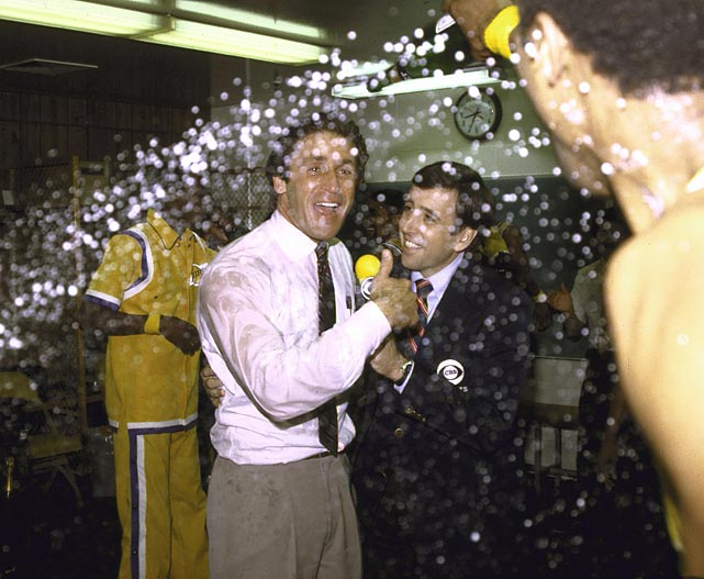 Musburger evades champagne sprayed by Kareem Abdul-Jabbar as Musburger interviews Los Angeles Lakers head coach Pat Riley. The Lakers beat the Philadelphia 76ers to win the 1982 NBA Championship.