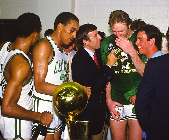 Musburger interviews Larry Bird amid a crowd of Celtics players after Boston beat the Los Angeles Lakers in Game 7 of the 1984 NBA Finals.