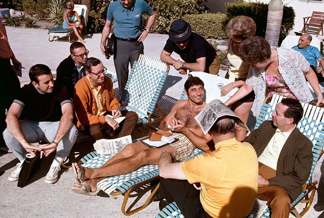 Musburger (far left) is among the reporters and fans chatting poolside with Joe Namath before Super Bowl III.