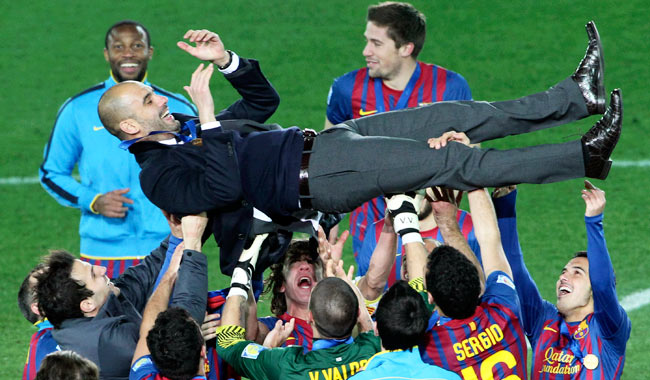 Barcelona players lift their manager Pep Guardiola after winning the Club World Cup in Dec. 2011.