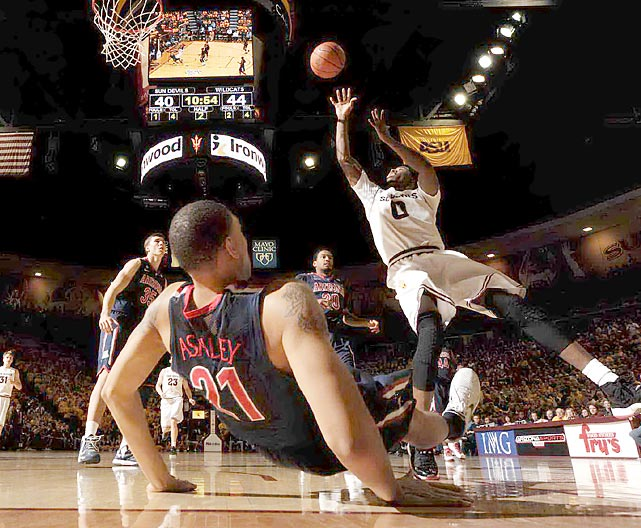 Arizona forward Brandon Ashley hits the floor as Arizona State's Carrick Felix puts up an off-balance shot in the Pac-12 rivals' Jan. 19 contest. After a close first half, the Wildcats ran away with the game, downing the Sun Devils 71-54.