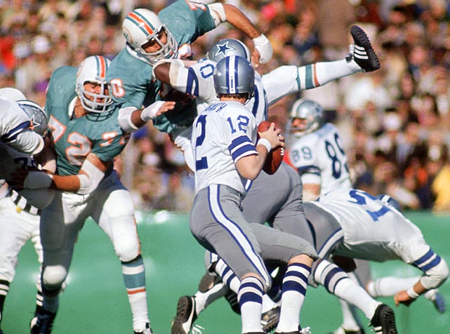 Roger Staubach sets to pass against the Miami Dolphins. Although the Dallas Cowboys quarterback was outdueled by the Dolphins' Bob Griese in passing yards, Staubach claimed the more important victory, snapping the Cowboys' reputation for being unable to win important playoff games.