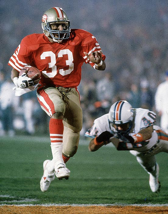 San Francisco 49ers running back Roger Craig rushes past a diving Miami Dolphins defender for a touchdown in his team's 38-16 win. Craig became the first player to score three touchdowns in a Super Bowl, catching two and rushing for a third.