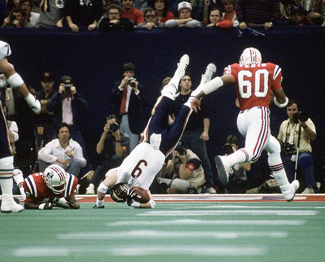 Chicago Bears quarterback Jim McMahon is upended on a scramble by the New England Patriots defense. McMahon became the first quarterback to rush for two touchdowns in a Super Bowl; he threw for 256 yards in the 46-10 rout.