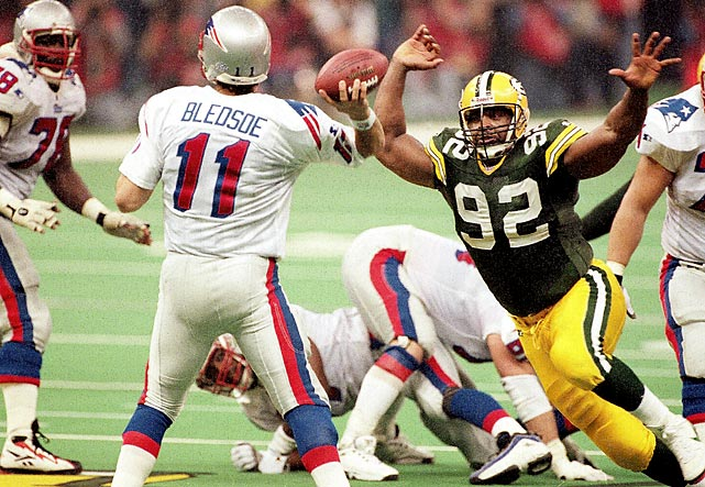 Green Bay Packers defensive end Reggie White bears down on Drew Bledsoe as the New England Patriots quarterback attempts to pass. The Green Bay Packers defense badly flustered Bledsoe as he threw four interceptions in the Pats' 35-21 loss. White set a Super Bowl record with three sacks.