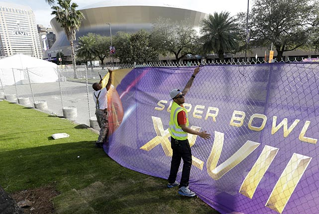 Emmanuel Joiner, left, and Kendrick Mills secure a screen over a fence as crews prepare for the Super Bowl.