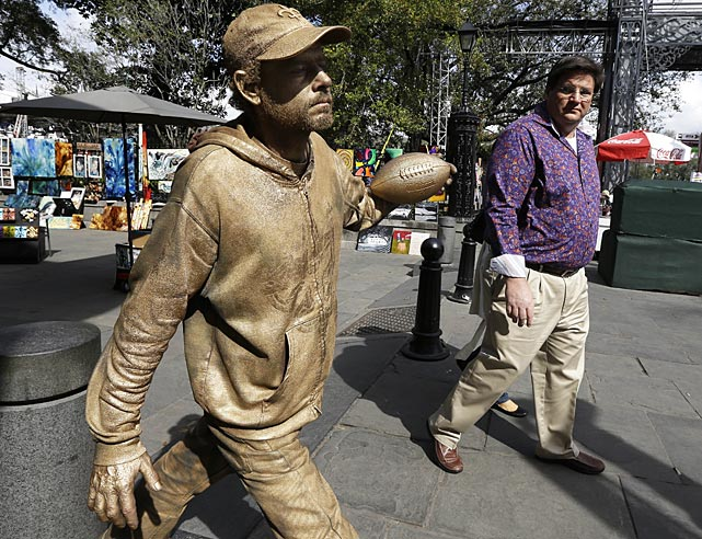 Street performer Tim Evans holds a football as he poses as a statue.