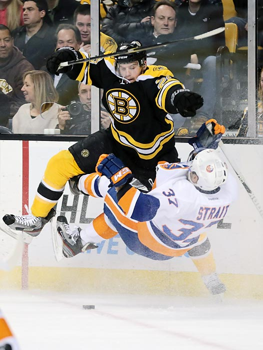 Boston Bruins left winger Daniel Paille lays out New York Islanders defenseman Brian Strait in Boston and New York's Jan. 25 game. Paille had an assist as the Bruins earned the victory, 4-2.