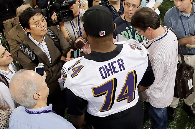 Michael Oher talks to a throng of reporters, including SI's Don Banks (immediate right).