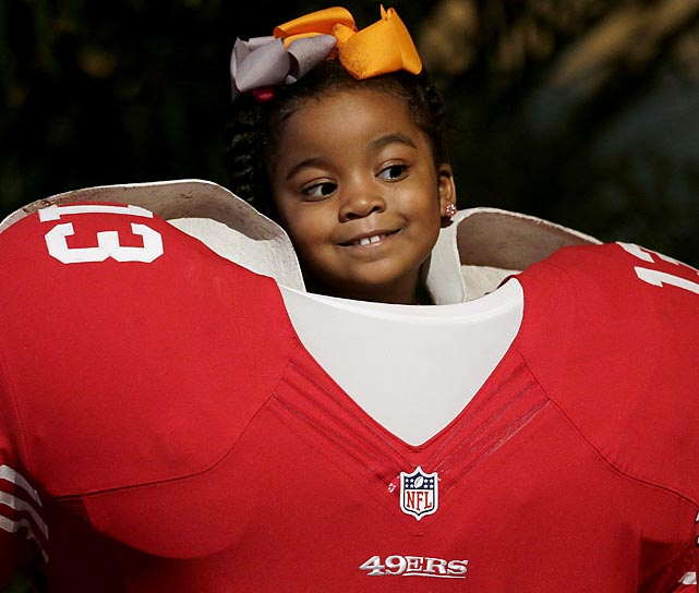 Perched above a cutout of a San Francisco 49ers football player, four-year-old Saniya Richardson, from New Orleans, poses for a photo at the NFL experience.