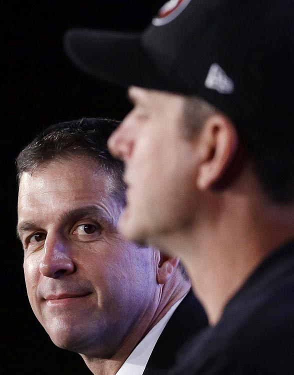 Baltimore head coach John Harbaugh watches his younger brother Jim answer a question at a joint news conference on Friday.