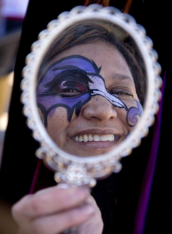 Jane White, of Franklin, Tenn., looks in a mirror at her new face painting of a Baltimore Ravens logo.