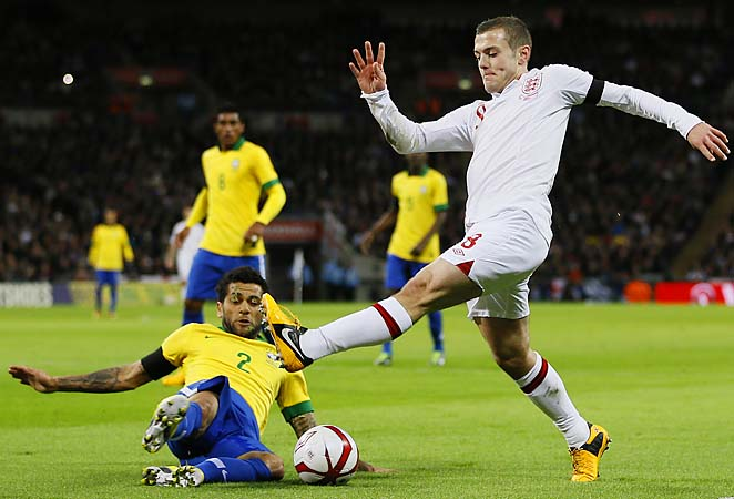 England's Jack Wilshere is tackled by Brazil's Daniel Alves at Wembley Stadium.