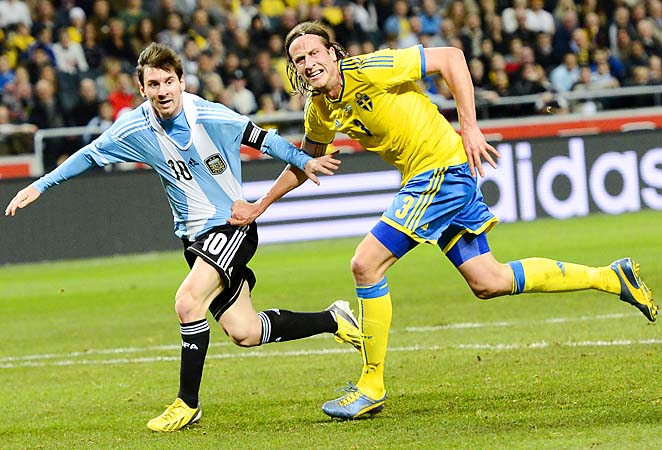 Lionel Messi vies with Sweden's Jonas Olsson in Solan, Sweden.