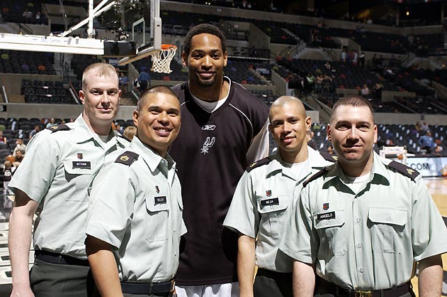 Robert Horry takes time to pose before a 2005 Spurs-Hawks game with Sgt. Jonathon Witham, Staff Sgt. Brian L. Miller II, Staff Sgt. Marlow Mejia and Sgt. Daniel Angelo during Military Appreciation Night in San Antonio.