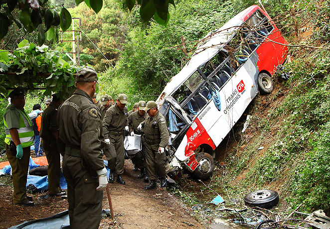 Officials look over the bus crash that killed 16 fans and injured 21 in Santiago.
