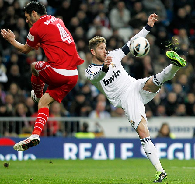 Real Madrid defender Sergio Ramos lifts for a ball against Sevilla defender Emir Spahic during the clubs' Spanish La Liga match in Madrid on Feb. 9. Real Madrid thoroughly dominated Sevilla 4-1 behind a superb, three-goal performance from Cristiano Ronaldo at the Santiago Bernabeu.
