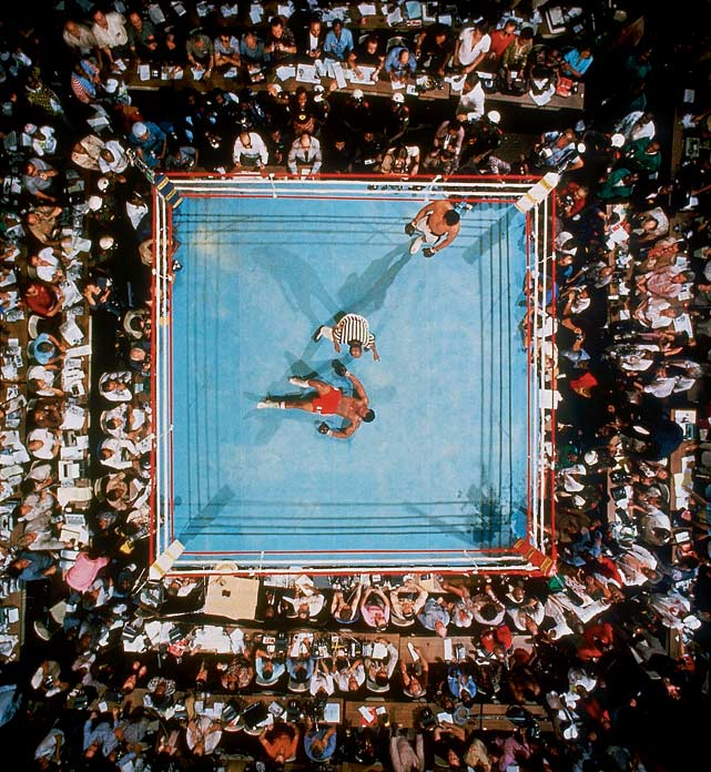 Employing his never-before-seen rope-a-dope strategy, even as his corner pleaded with him to move and dance, Ali let Foreman punch himself out, then came off the ropes firing big shots of his own. In a stunning finish he put Big George down for good in the eighth round. Here, the soon-to-be-ex-champ stares at the ceiling (and Leifer's lens) as referee Zack Clayton counts him out and Ali, having once again shocked the world, stands calmly by. Click here for Neil Leifer's fine art photography.