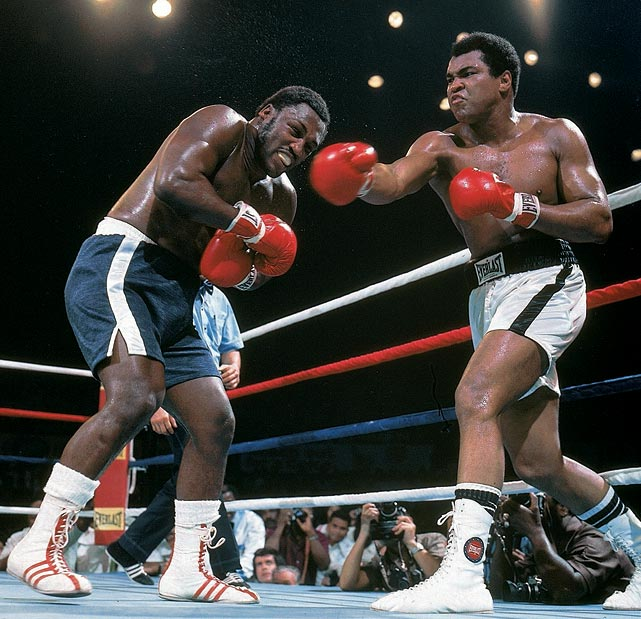 "The third fight between Ali and Frazier, held on Oct. 1, 1975, in Quezon City in the Philippines, proved to be one of the most dramatic and brutal bouts in heavyweight history. Both men absorbed tremendous punishment in the relentless back-and-forth battle. (Ali would later call it the ""closest thing to dying that I know of."") With his eye swollen shut, and no longer able to see Ali's punches coming, Frazier rose from his stool for the 15th and final round, but his trainer, Eddie Futch, called the fight off, giving Ali the victory. ""Sit down, son,"" Futch said to Frazier. ""No one will ever forget what you did here today."" Click here for Neil Leifer's fine art photography."