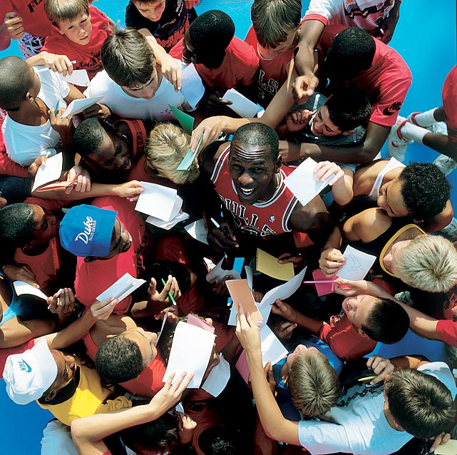 Young autograph seekers surround Jordan at a basketball camp in March 1987. With his on-court success and successful off-court marketing, Jordan quickly became one of the NBA's biggest stars.