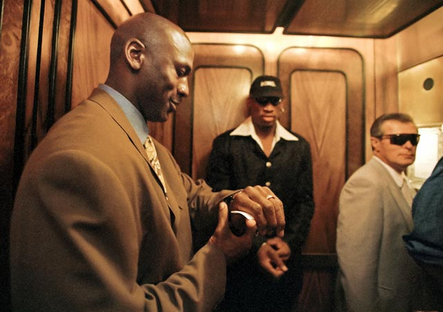 Michael Jordan checks his watch in a Houston hotel elevator with Dennis Rodman and security personnel in April 1998.