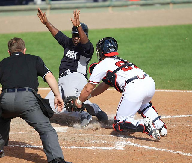 Atlanta Braves catcher Jose Yepez applies the tag to the New York Yankees' Jose Pirela at home plate in a spring training game on Feb. 23 in Orlando, Fla. The Yankees won their spring training-opener 8-3, getting home runs from Zoilo Almonte and Robinson Cano.
